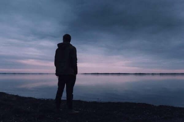 Mann står ved havet