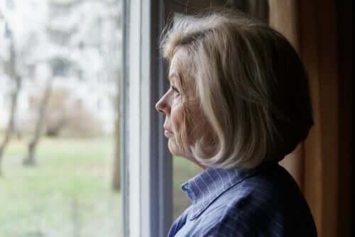 Eldre kvinne ser ut av et vindu