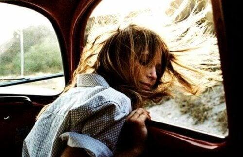 Glad kvinne ser ut bilvindu