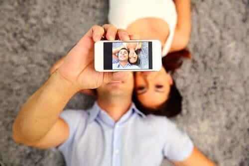 En mann som tar en selfie av seg selv og en kvinne.