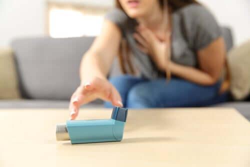 En kvinne som strekker seg etter inhalatoren sin