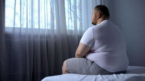 Overvektig mann sitter på en seng
