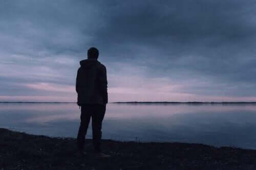 Mann ser utover en sjø i solnedgang.