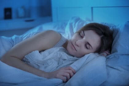 Kvinne som sover godt i sengen sin