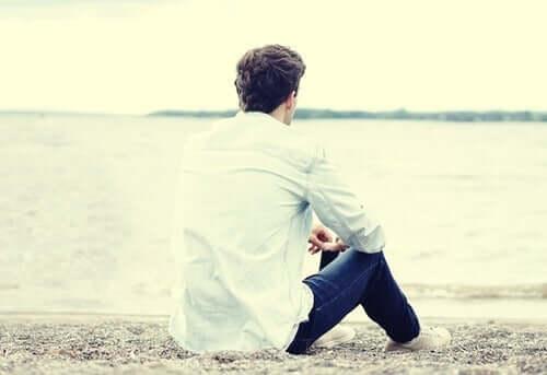 Mann sitter på stranda