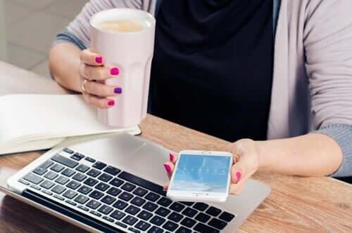 Kvinne med mobiltelefon og datamaskin