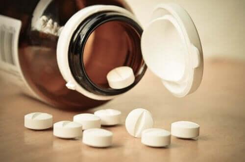 En åpen pilleflaske som ligger på siden, med noen piller på bordet.