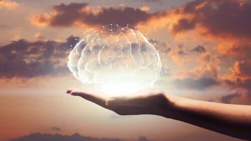 En hånd med et holografisk hjernebilde som projiserer over den.