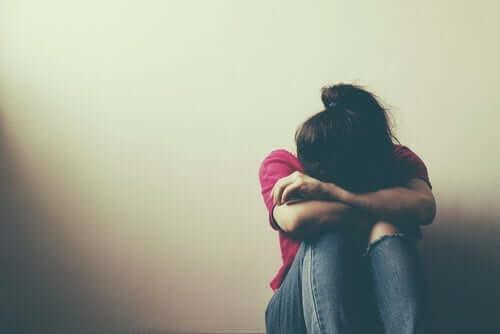 En jente som gråter med hodet i armene.