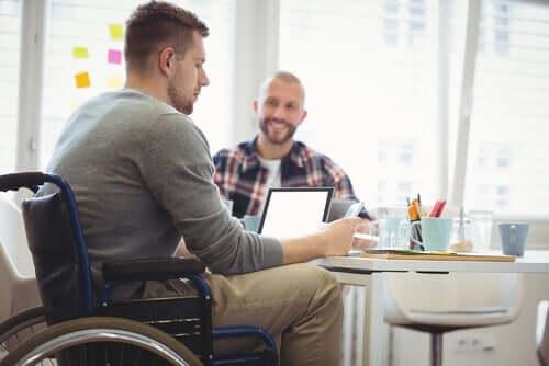En mann i rullestol som sitter ved et bord og arbeider på sin bærbare datamaskin.