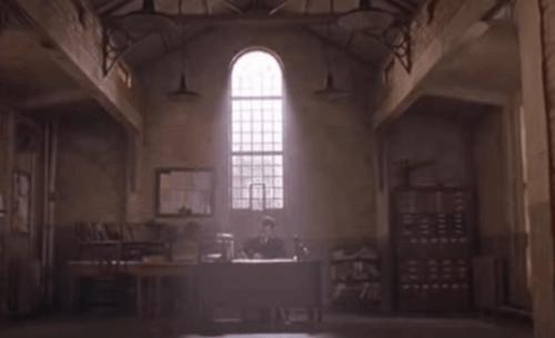 En mann som sitter ved et skrivebord i et muggent rom i et fengsel.