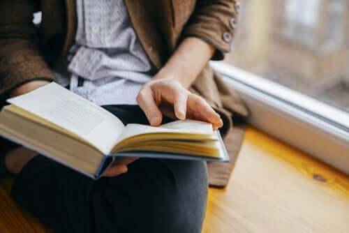 En person som leser ved vinduet.