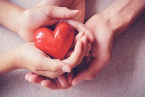 Fire hender som holder et hjerte.