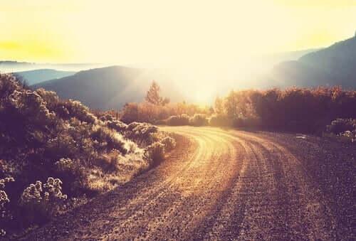 Solen som skinner over fjellet på en vei