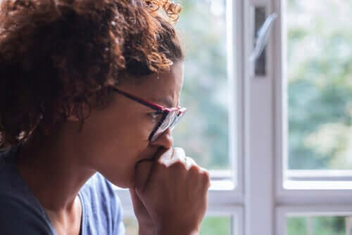 Bekymret kvinne ved vindu