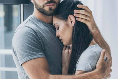 Mann holder rundt trist kvinne