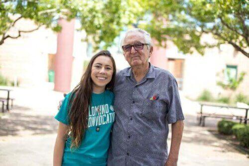 En gammel mann som klemmer en yngre kvinne.