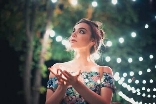 En kvinne omgitt av lys.