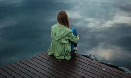 En kvinne på en brygge foran havet.