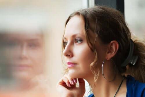 En kvinne som ser ut av vinduet og tenker på moralske dilemmaer.