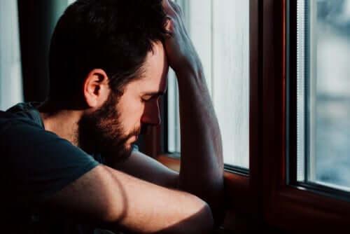 En mann med angst som lener seg mot vinduet.