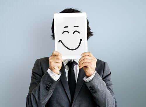 En mann som holder et lykkelig ansikt tegnet på et papir.