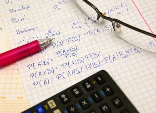 En sannsynlighetseksamen med en kalkulator, en penn og et par briller.