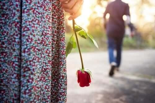 En mann som går fra en kvinne som holder en rose