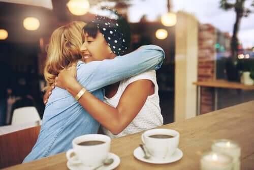 To veninner gir hverandre en ordentlig klem på en café