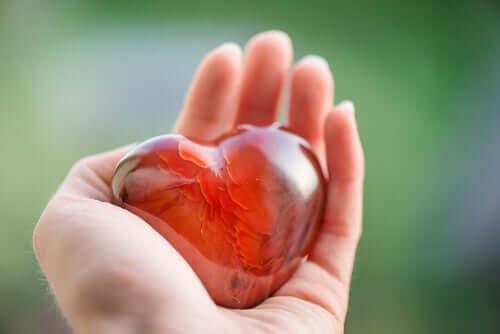 En hånd som holder et rødt glasshjerte