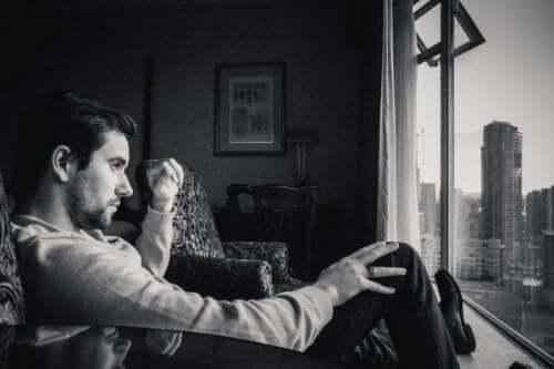 Et svart hvitt bilde av en mann som ser ut av stuevinduet på storbyen utenfor