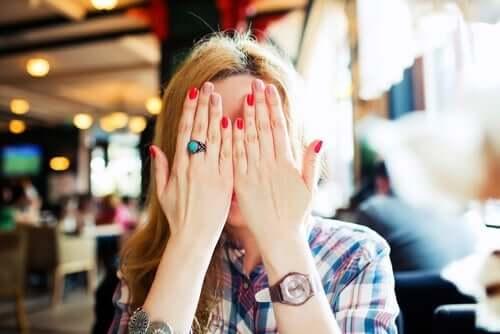 En kvinne med hendene foran ansiktet