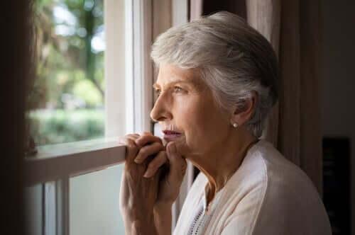 En eldre kvinne som ser ut av vinduet.