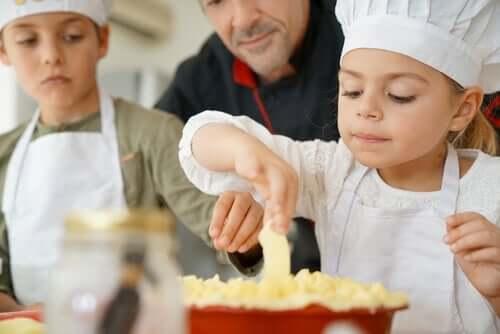 En jente og en gutt som lager mat sammen med faren sin.
