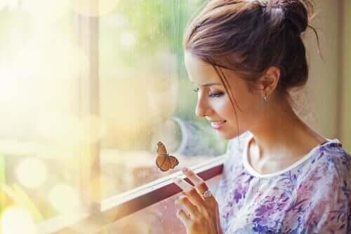 En kvinne som smiler til en sommerfugl på vinduet.