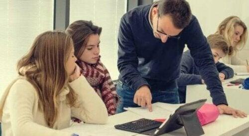 En lærer som ser på en elevs arbeid.