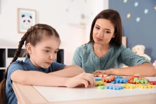 En lærer som ser på en jente leke.