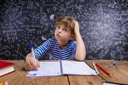 En liten gutt som studerer matematikk.