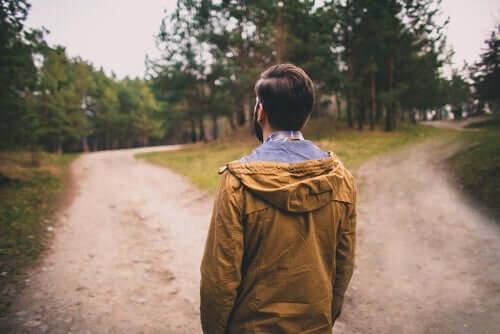 En mann foran to veier som representerer forskjellige beslutninger.