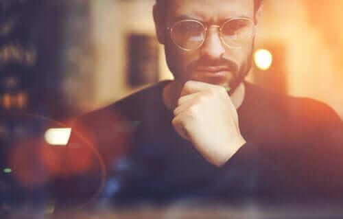 En mann med briller muligens engasjert i dyp kontrafaktuell tenking.