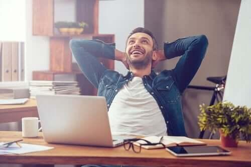 En mann som sitter ved et skrivebord og ser lykkelig ut.