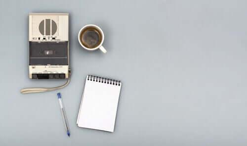 En opptaker ved siden av en kopp kaffe, en notatbok og en penn.