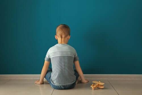 Et barn som sitter foran en vegg med et leketøyfly.