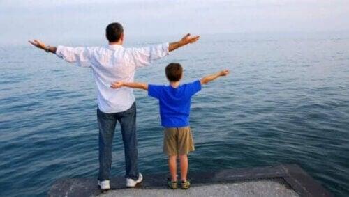 Far og sønn med utstrakte armer foran vann.