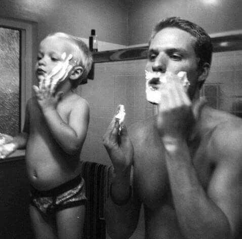 Far og sønn påfører barberskum.