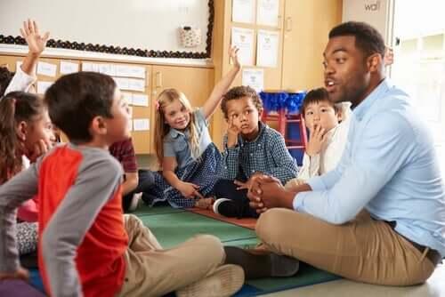 Lærer omringet av barn i klasserom.