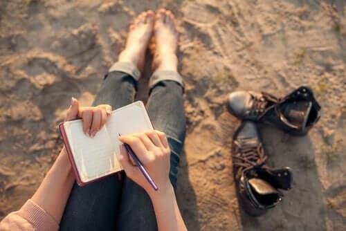 Kvinne sitter barfot på en strand og skriver dagbok