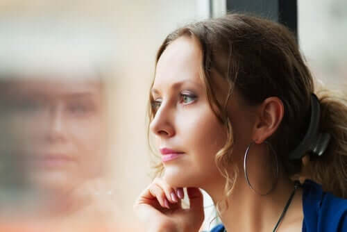 Kvinne ser ut av vindu og på sitt eget speilbilde