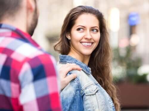 Ung kvinne smiler mot en mann som legger hånden på skulderen hennes