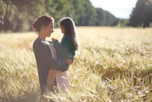 Mor som holder datter på et jorde.